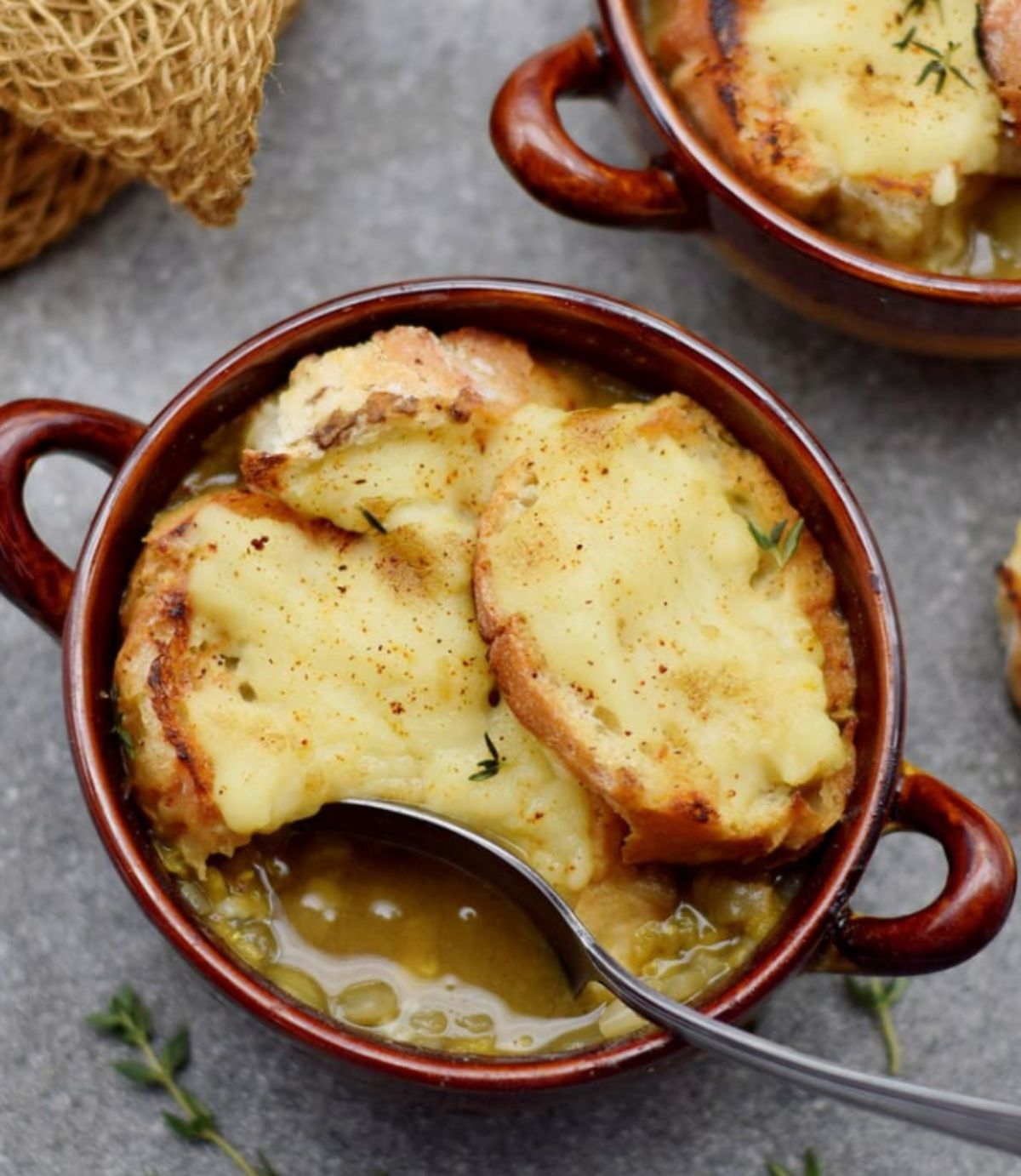 a small red casserole dish filled with french onion soup.