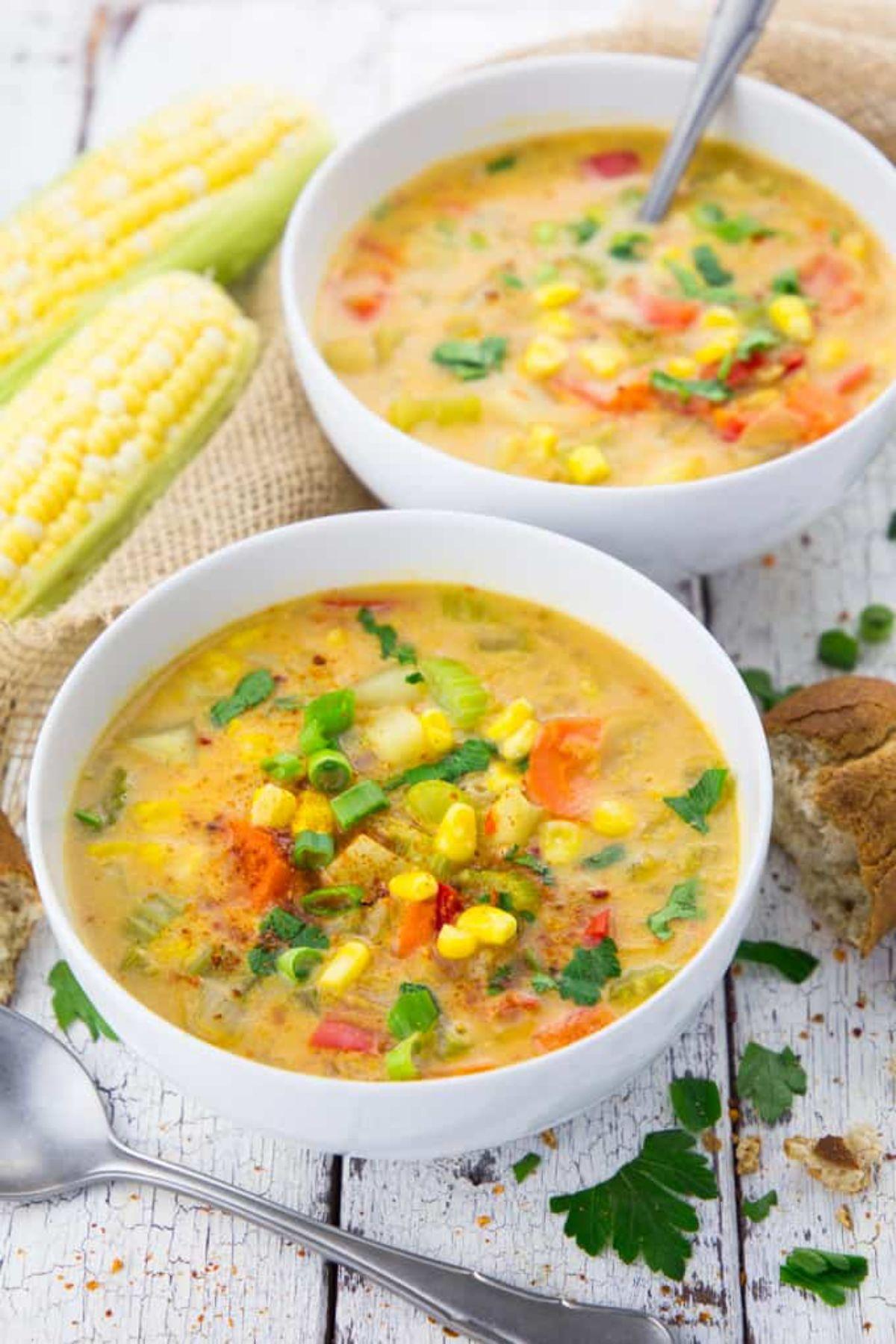 2 bowls full of vegan corn chowder. ears of corn sit behind
