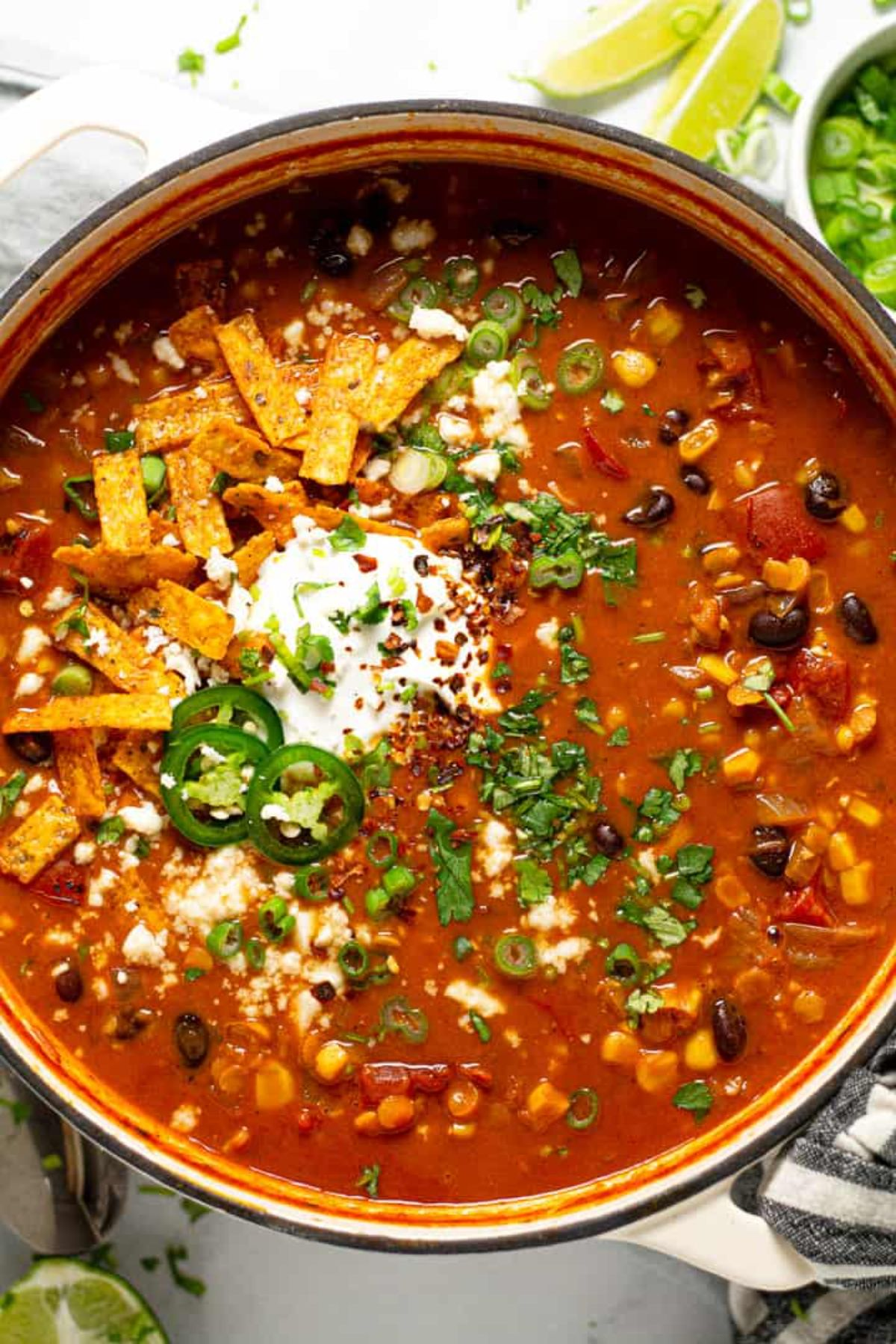 a pan full of lentil tortilla soup topped with chopped herbs, sliced tortillas and jalapeno slices