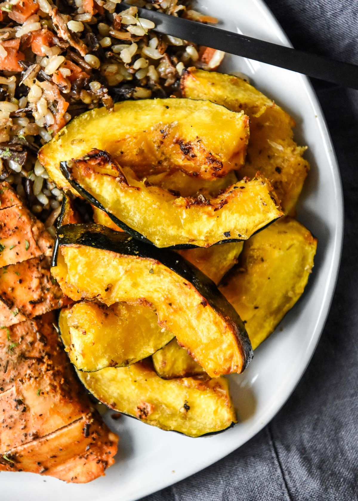 a partial view of a plate full of acorn squash slices next to a pile of grains