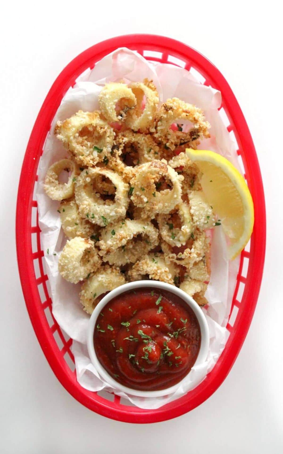 a top view of a red woven basket filled with vegan calamari rings next to a lemon slice and a bowl of red sauce