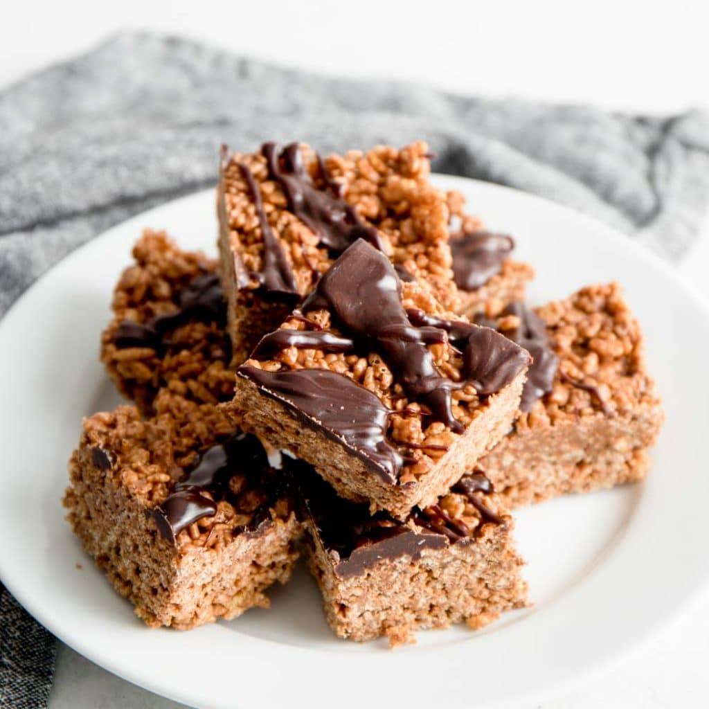 Peanut Butter Chocolate Rice Krispie Treats on a white plate with chocolate drizzle