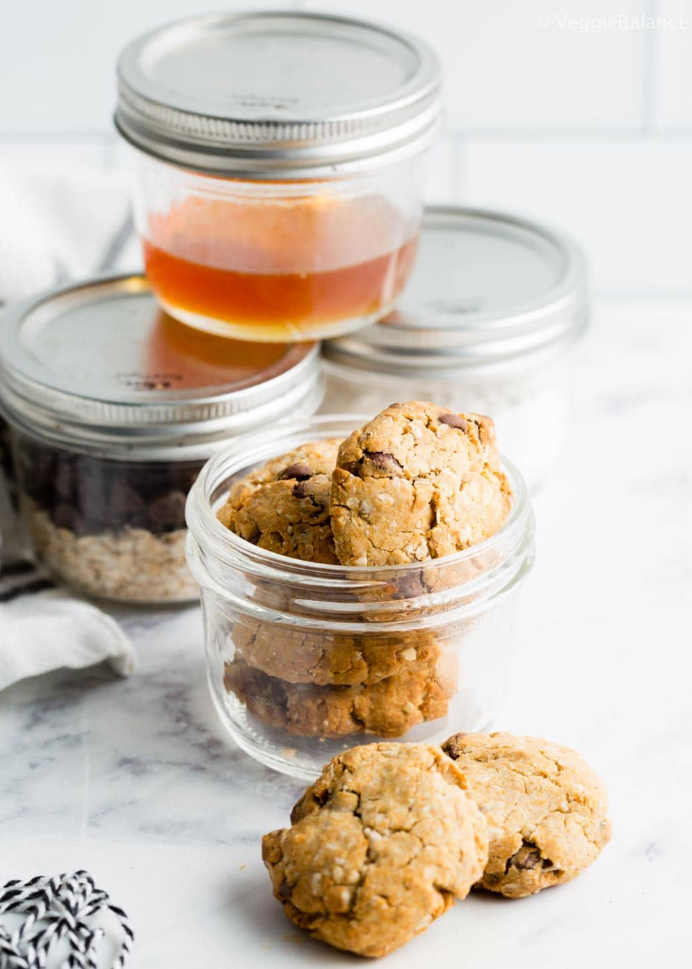 Oatmeal Cookies in Jar with ingredients in jars in the background