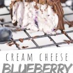 """PINTEREST IMAGE with words """"Cream Blueberry Cheese Truffles"""" Cream Blueberry Cheese Truffles on a cooling rack with one missing a bite"""