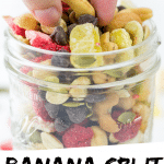 "PINTEREST IMAGE with words ""Banana Split Trail Mix"" Image Banana Split Trail Mix in a glass jar with a pinch full being lifted out."