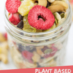 "PINTEREST IMAGE with words ""Plant Based Banana Split Trail Mix"" Image Banana Split Trail Mix in a glass jar with overflow spread around,"
