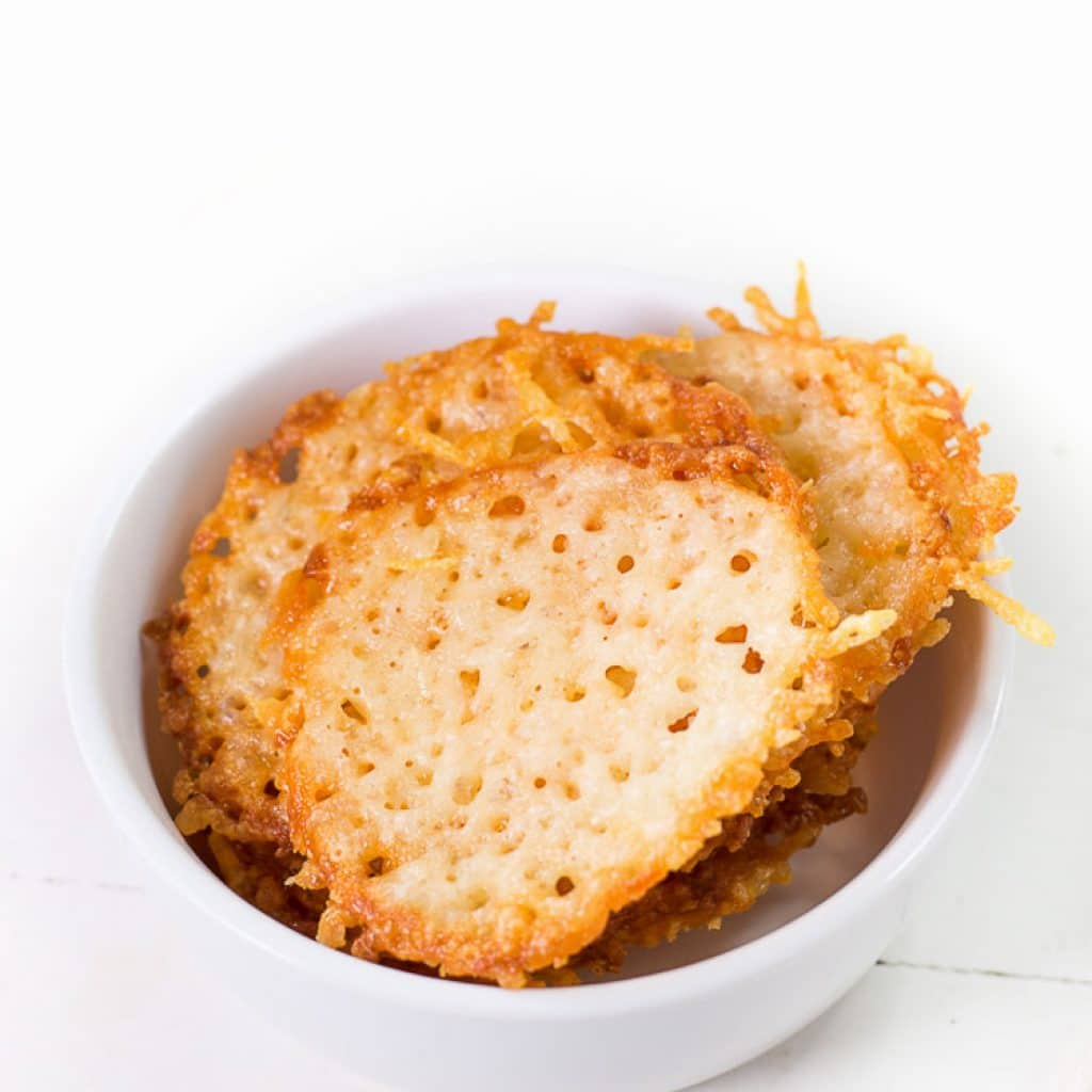 baked parmesan cheese crisps in a white bowl