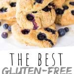 "PINTEREST IMAGE with words ""The Best Gluten-Free Blueberry Scones"" The Best Gluten-Free Blueberry Scones piled on a plate with blueberries on the edge"