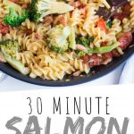 "PINTEREST IMAGE with words ""30 Minute Salmon Cajun Pasta"" Salmon Cajun Pasta in a skillet with broccoli"