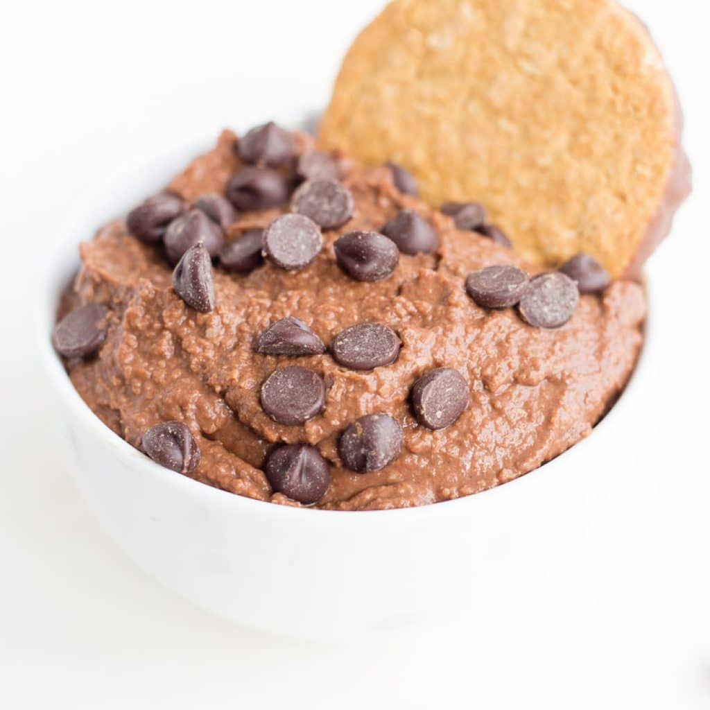 Brownie Batter Chocolate Hummus in small white bowl with chocolate chips and a cookie on top.