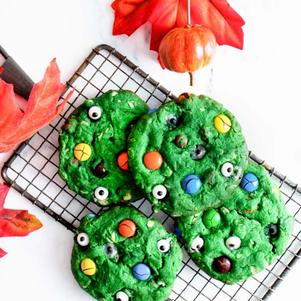 Overhead shot of Halloween Monster Cookies green cookies with M&M's and eye candies on top piled on a cooling rack