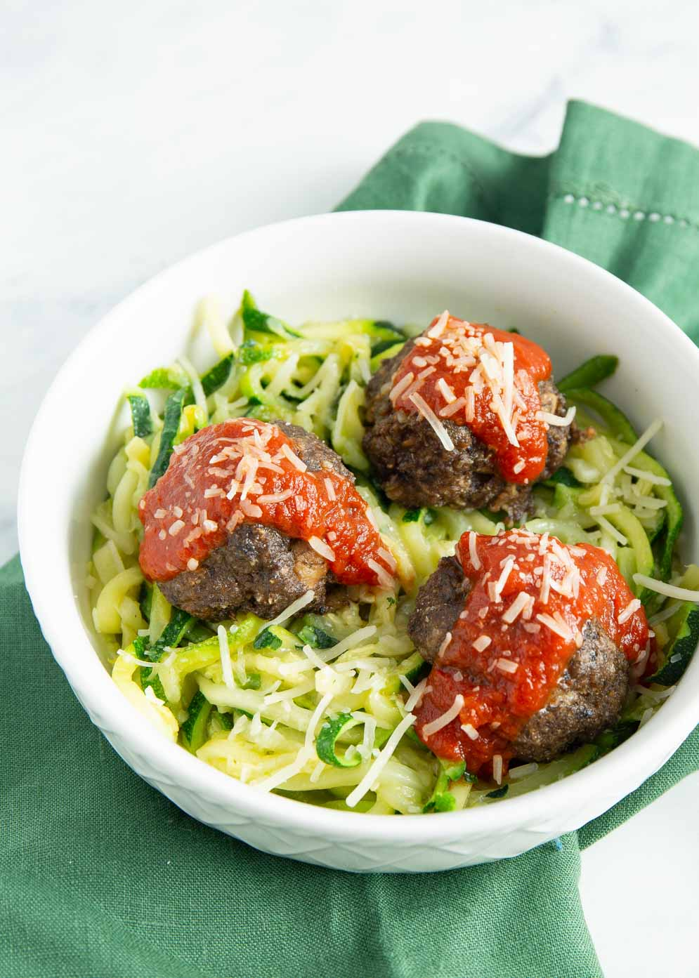 Vegetarian Meatless Meatballs with red sauce on top in a white bowl a top greens