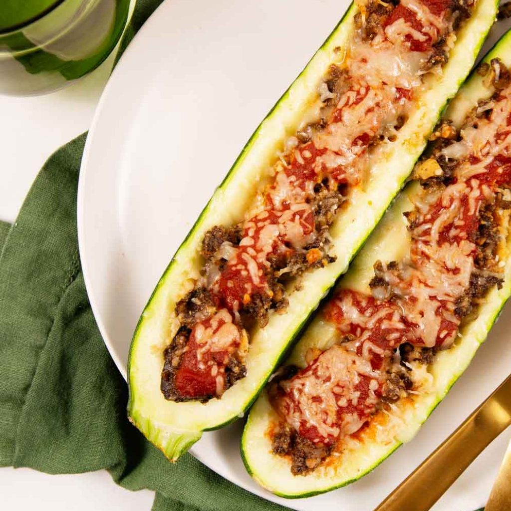 Italian Vegan Stuffed Zucchini Boats on a white plate on a green tea towel