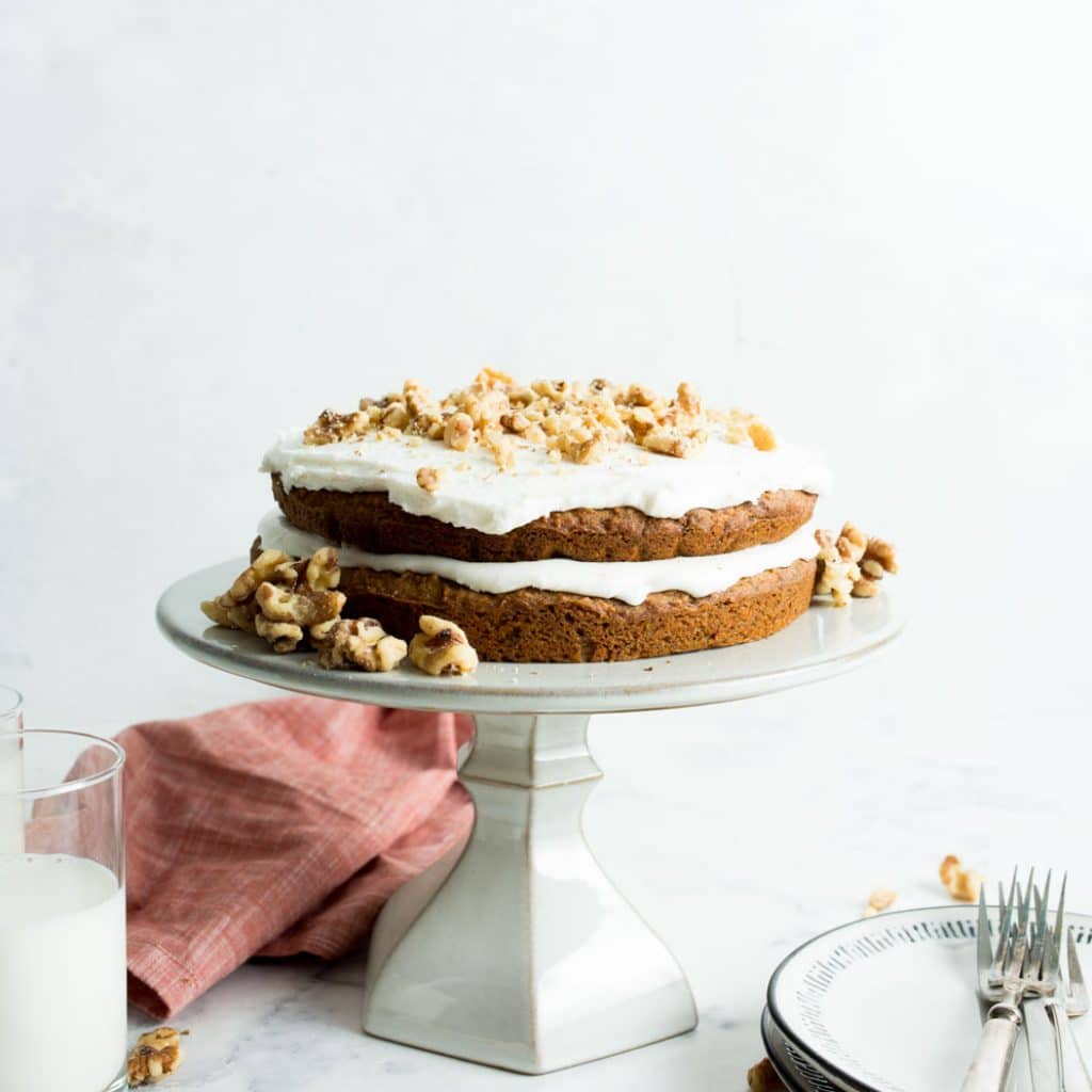 Vegan Carrot Cake on a white cake stand with two glasses of milk and a stack of plates.