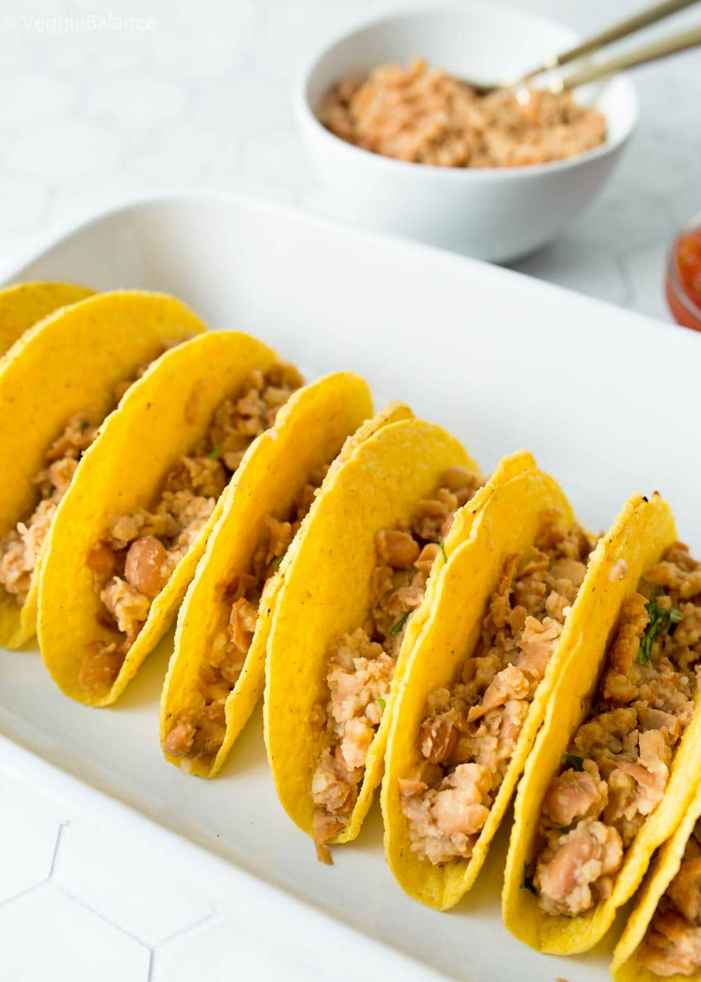 Taco shells stuffed with refried beans as first layer of vegetarian tacos