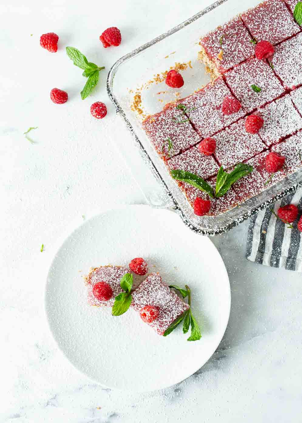 Overheat shot of pan of vegan raspberry bars and a small white plate in lower left corner with two bars all decorated with fresh raspberries