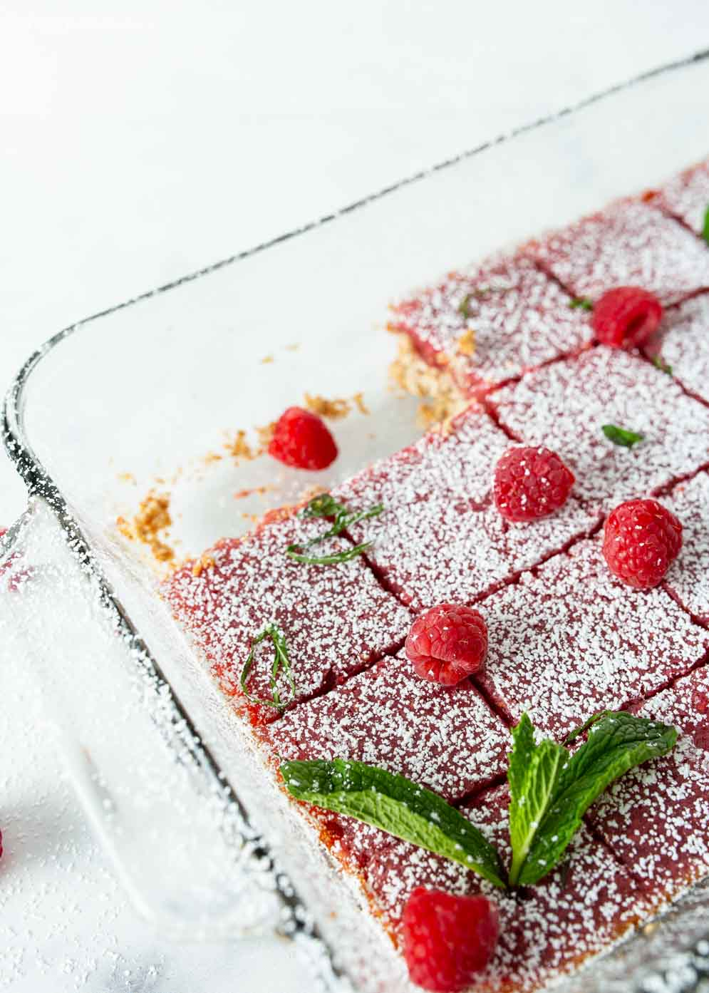 Pan of Vegan Raspberry Lemon Bars with two squares taken out and decorated with powdered sugar and fresh raspberries