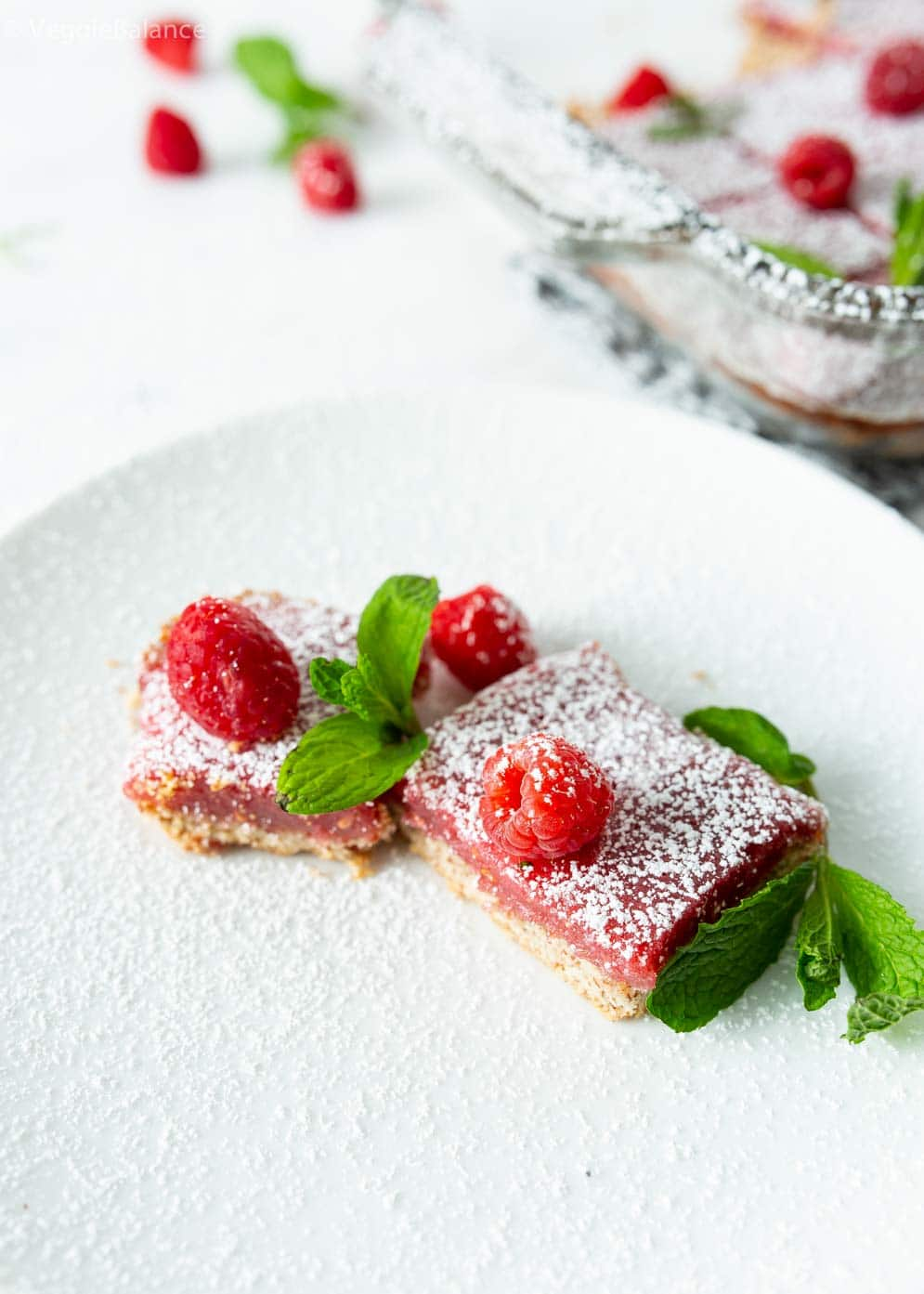 Two Vegan Raspberry Lemon Bars with fresh raspberries and mint leaves decorated around on a small plate