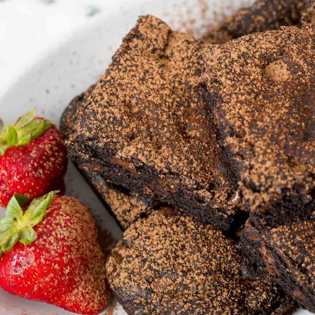 Plate of Vegan Brownies with strawberries on the side