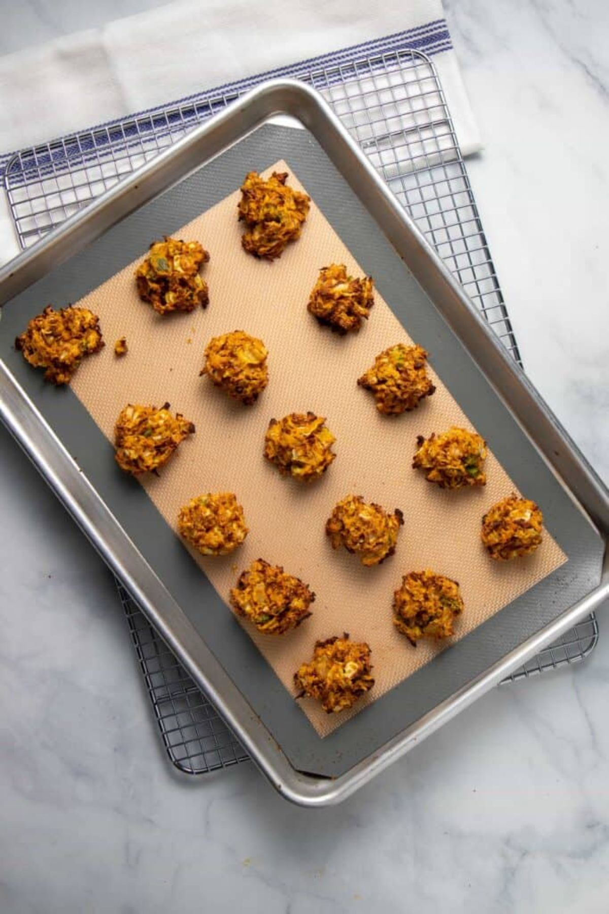 a top view of a baking tray with cabbage fritters laid out on it
