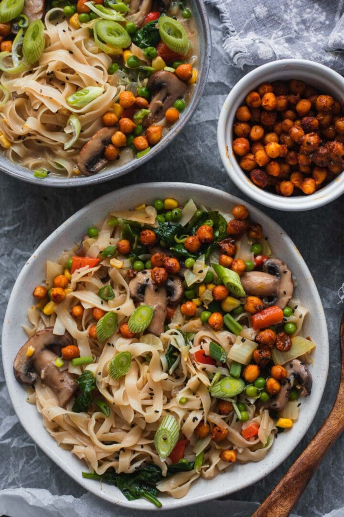 2 bowls full of noodle soup with roasted chickpeas. a bowl of chickpeas sits to the side