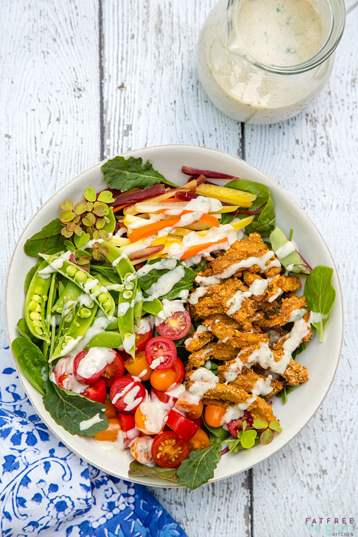 a white dish full of soy curls, green salad, and drizzled with salad dressing.