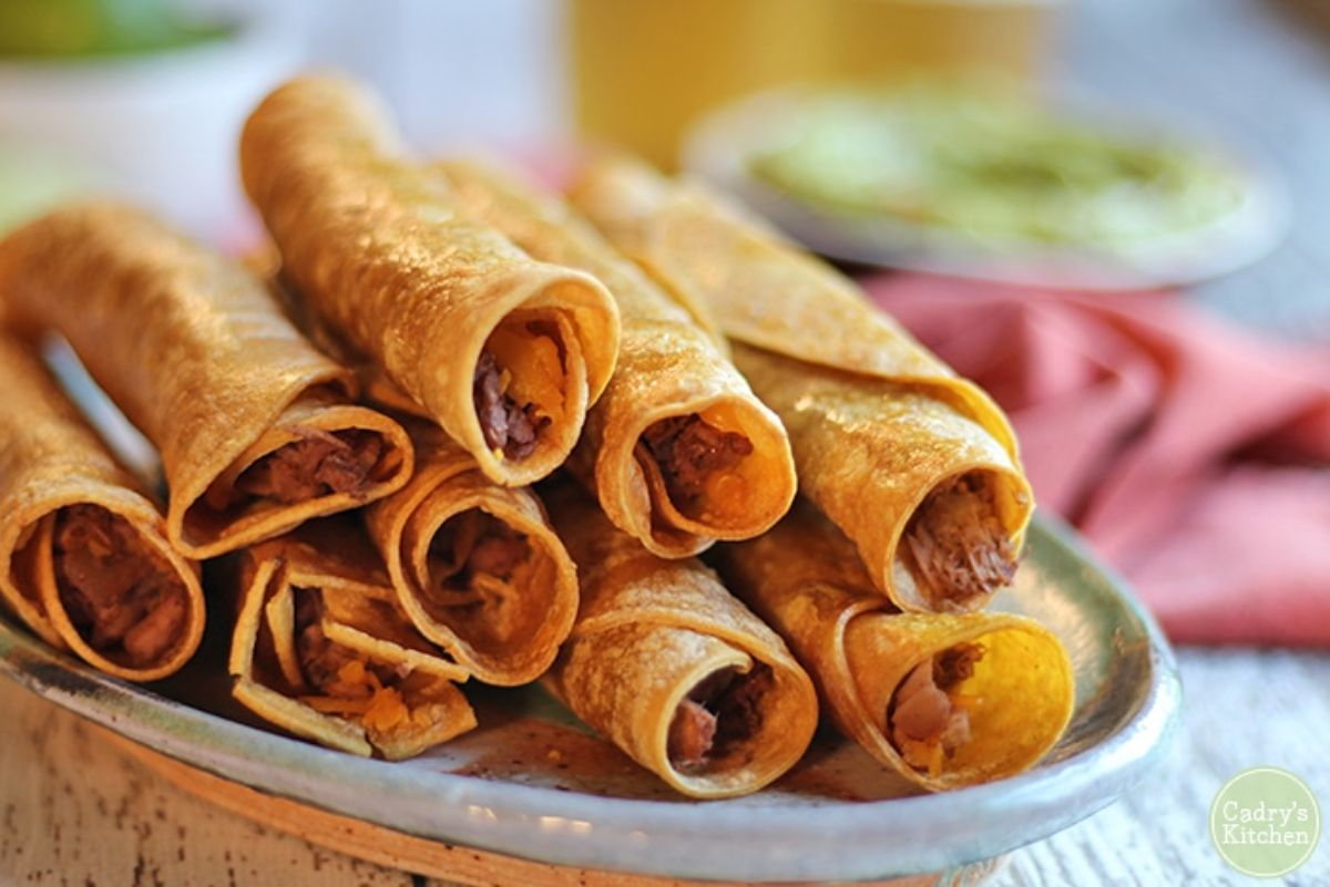 a pile of rolled taquitos sit on a grey plate