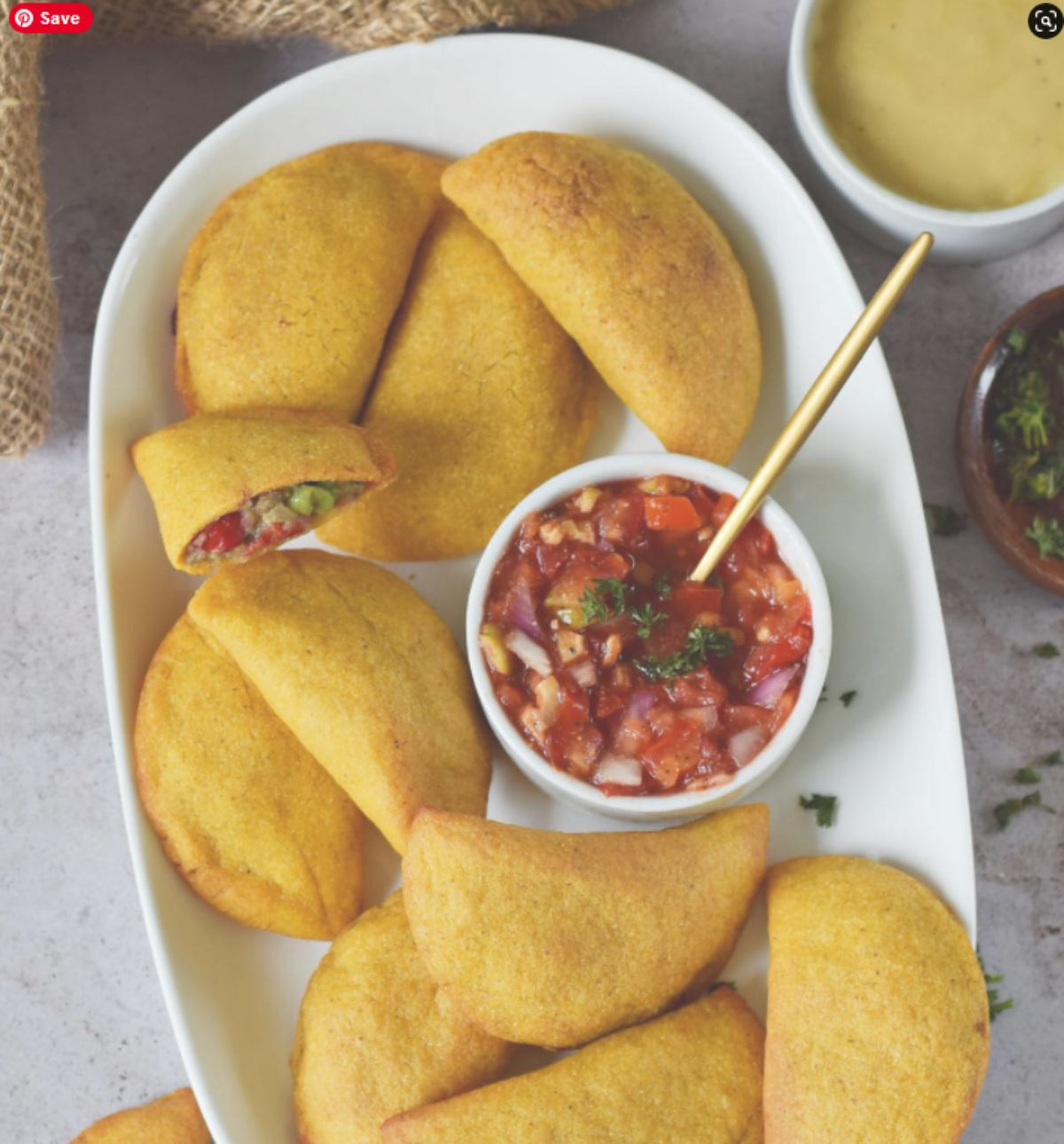 a white oval dish of empanadas with a bowl of salsa in the middle of the pile