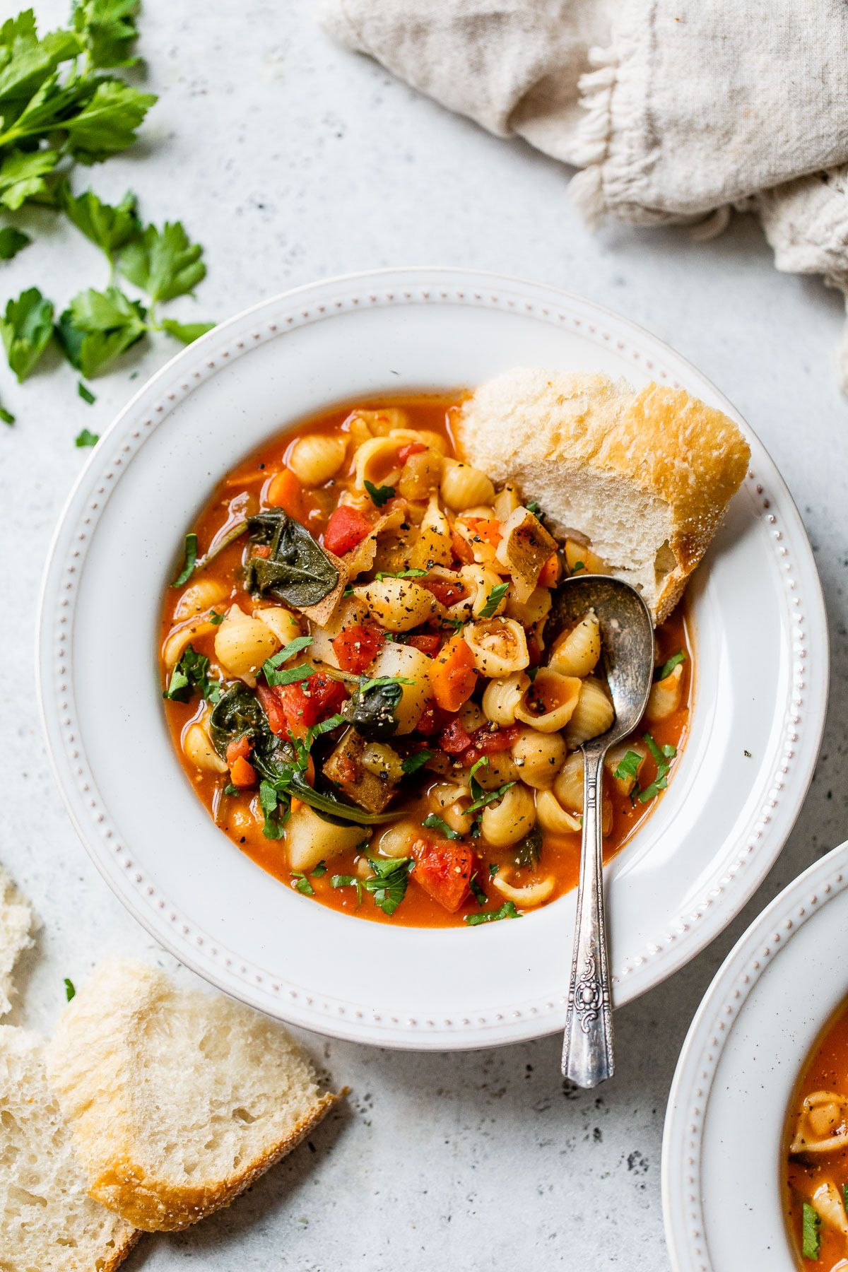 a white dish full of minestrone with a slice of bread on the side