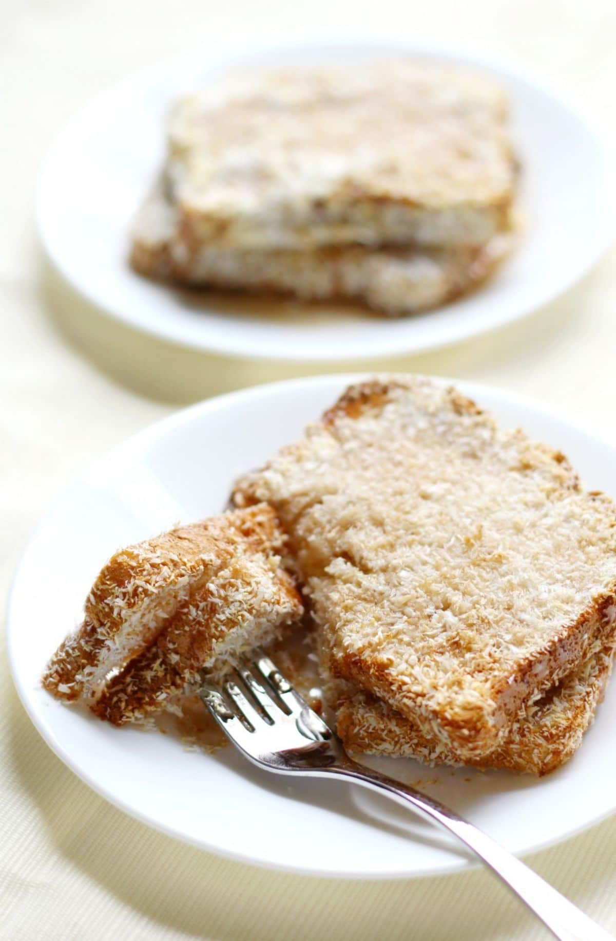 2 plates of coconut french toast. The nearest plate has a fork sticking into a portion of the slice