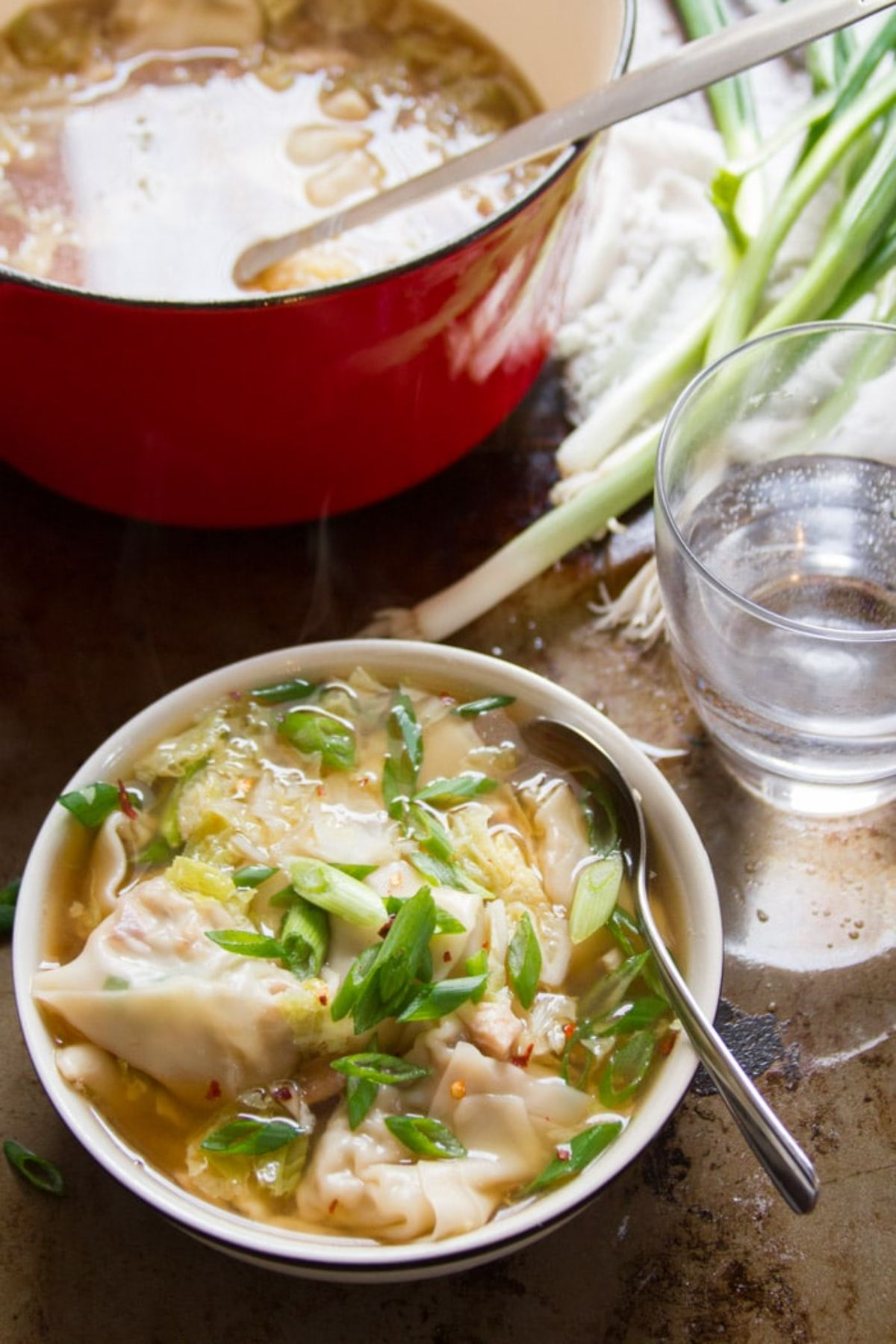 a casserole dish full of shiitake wonton soup with a bowl of the soup in front of it