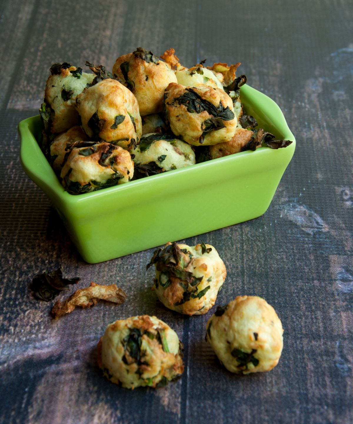 a green square casserole dish filled with potato and kale nuggets. Some have spilled out onto the gray surface